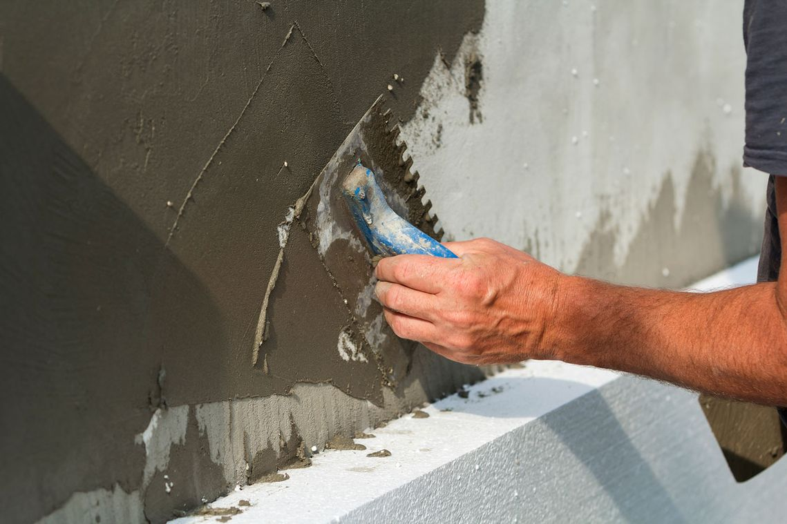 plasterer applying plaster to a wall