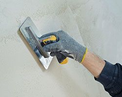 A plasterer skimming a plastered wall