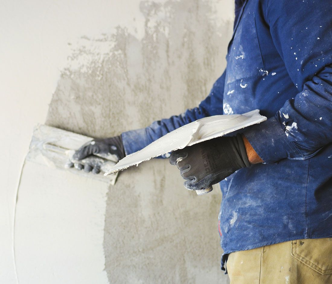 A plasterer, plastering a wall